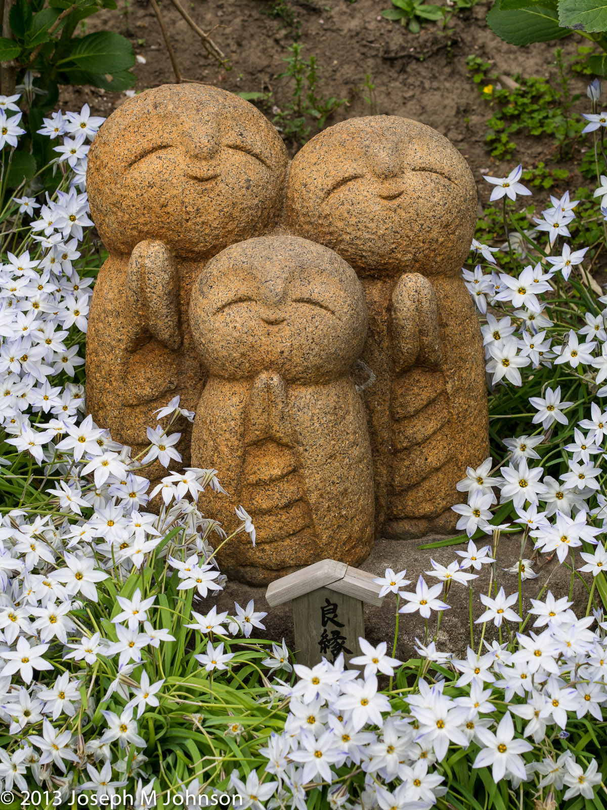 Cute statues cuddled in spring flowers