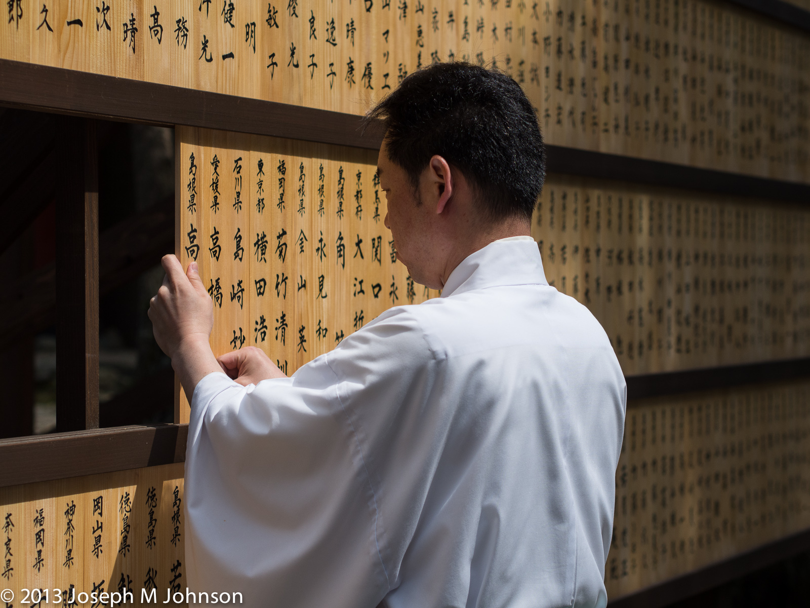 Shinto Priest rearranges names at donor wall in Izumo